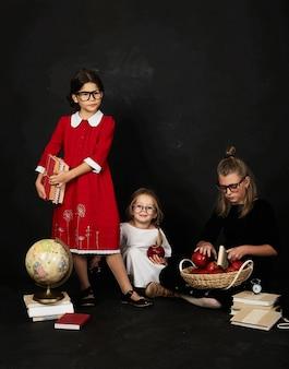 Três belas alunas de diferentes clases e pré escola menino em um fundo preto