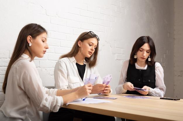 Três belas moças à mesa no escritório com dinheiro do euro