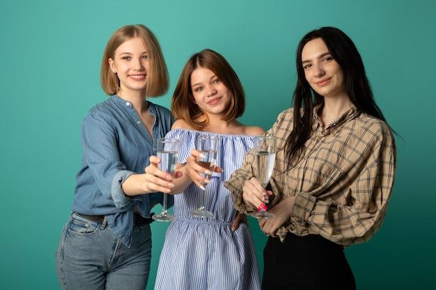 Três belas moças com taças de champanhe nas mãos Foto Premium