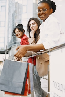 Três belas mulheres com sacos de presente andam na cidade. as mulheres depois das compras se divertem.