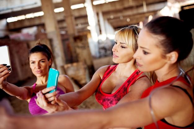 Três belas mulheres desportivas estão fazendo uma selfie em local abandonado.