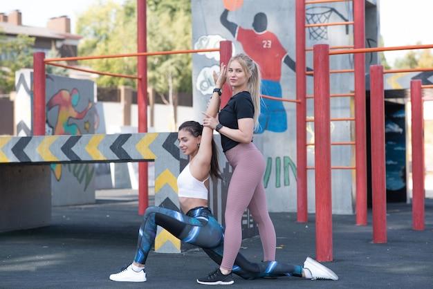 Três belas mulheres jovens e atléticas estão fazendo aquecimento no campo de esportes na rua