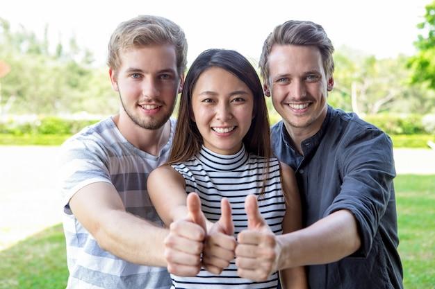 Três, bem sucedido, estudante, amigos, mostrando, polegares, cima