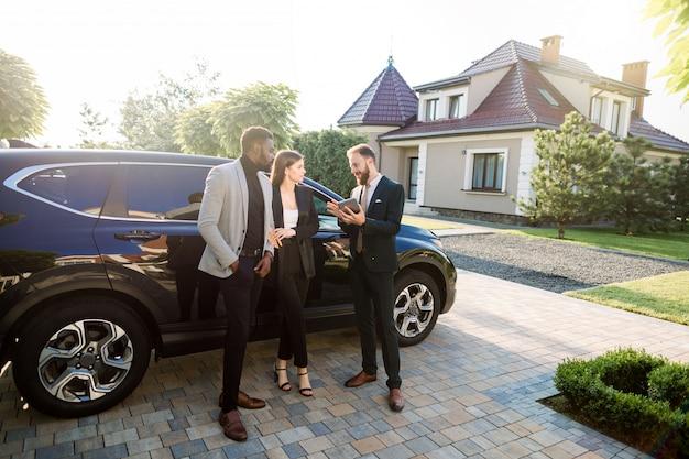 Três bem sucedidos empresários confiantes multiétnicas em roupas casuais inteligentes usando tablet perto de carro, em pé ao ar livre no quintal do moderno centro de negócios