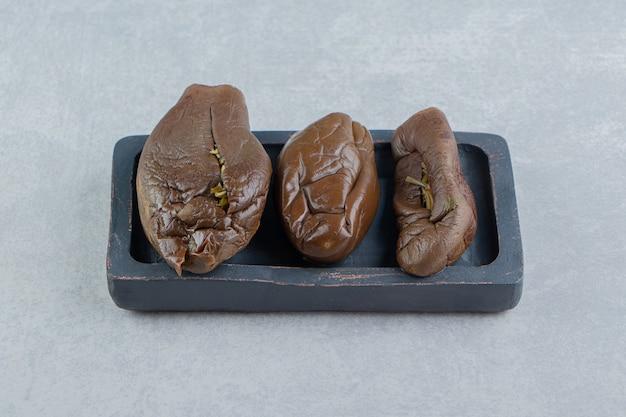Três berinjelas em conserva no tabuleiro, na superfície de mármore