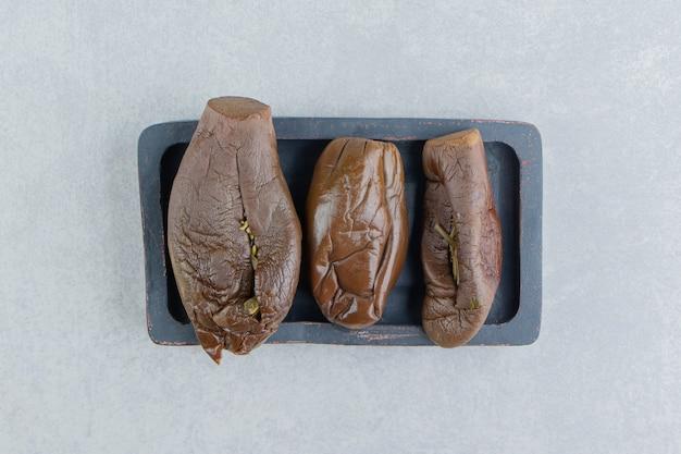 Três berinjelas em conserva no tabuleiro
