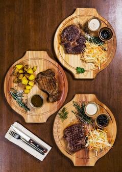 Três bifes de carne com legumes e verdura na mesa de madeira em um restaurante de luxo