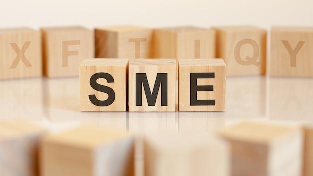 Três blocos de madeira de brinquedo com as letras sme em uma mesa com superfície clara. sme - abreviação de pequenas e médias empresas