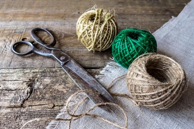 Três bolas de fio marrom e verde com uma tesoura