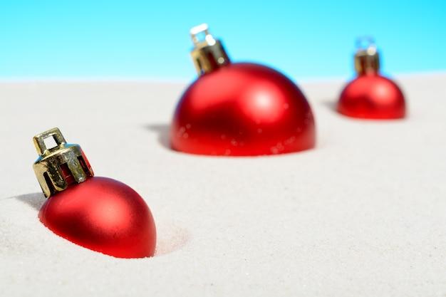 Três bolas de natal na areia da praia ensolarada