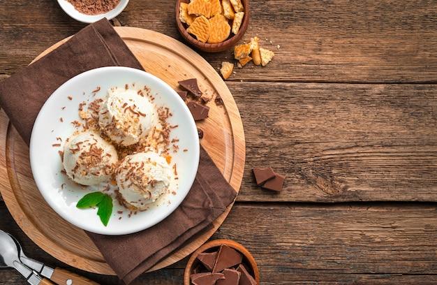 Três bolas de sorvete com gotas de chocolate e migalhas de biscoito em um prato branco em uma parede de madeira marrom com espaço para copiar. vista superior, horizontal.
