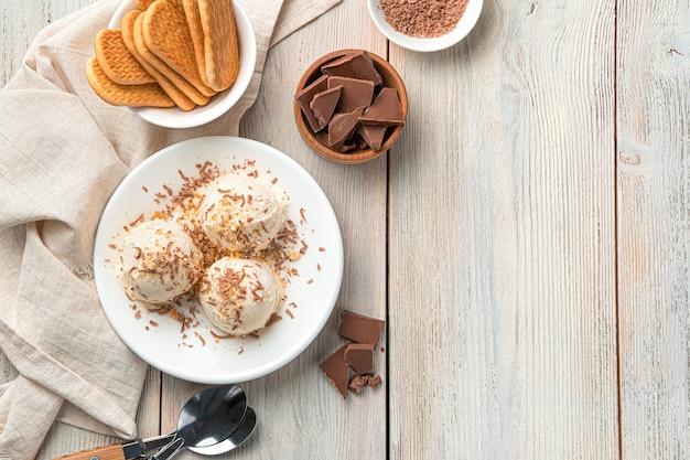 Três bolas de sorvete com gotas de chocolate e migalhas de biscoito em um prato branco sobre uma parede de luz