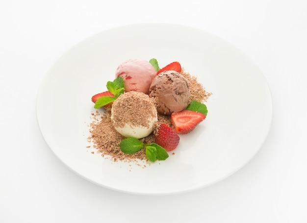 Três bolas de sorvete de chocolate, morango e baunilha com menta e gotas de chocolate