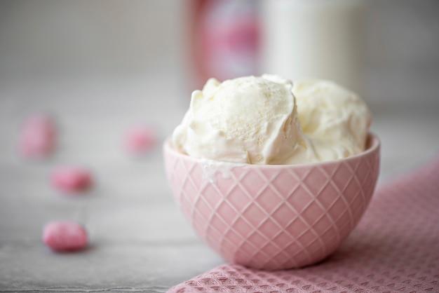 Três bolas de sorvete de creme branco em uma tigela rosa