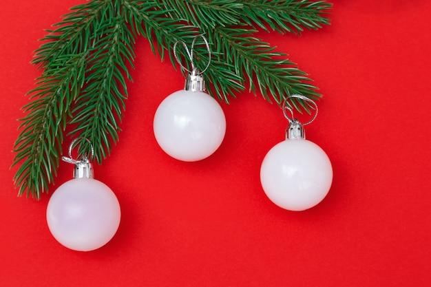 Três bolas de vidro de natal branco em galhos verdes sobre fundo vermelho