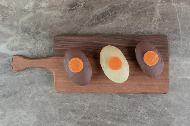 Três bolos com geléias em tábua de madeira