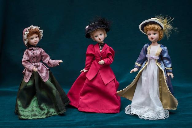 Três bonecas em vestidos vintage clássicos e chapéus no escuro