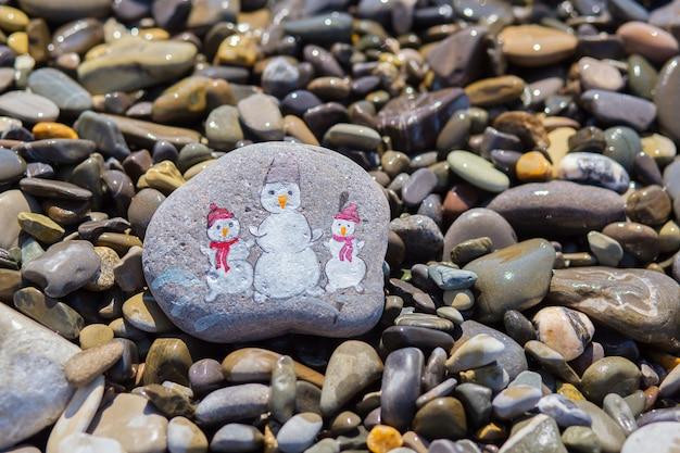 Três bonecos de neve pintados com aquarela em seixo de praia no mar