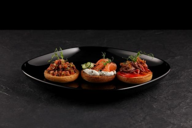 Três bruschetas redondas com diferentes sabores e ingredientes (peixes, vegetais, carnes).