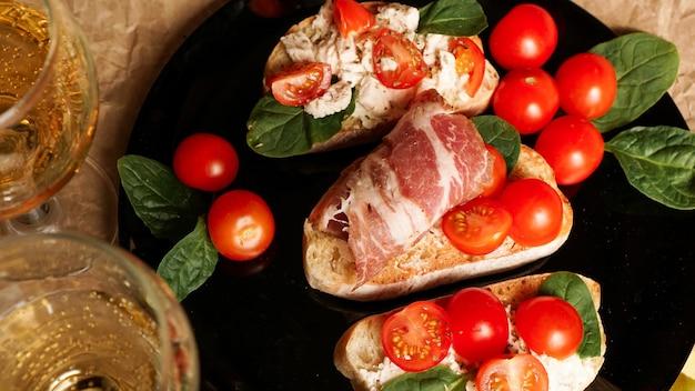 Três bruschettas em uma placa preta no papel ofício. aperitivo com tomate cereja, requeijão, espinafre e bacon com taças de vinho ou champanhe
