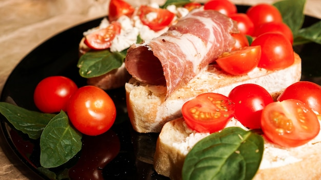 Três bruschettas em uma placa preta no papel ofício. aperitivo com tomate cereja, requeijão, espinafre e bacon.