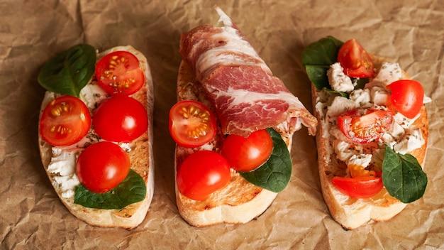 Três bruschettas frescas em papel artesanal deliciosos lanches vista de cima