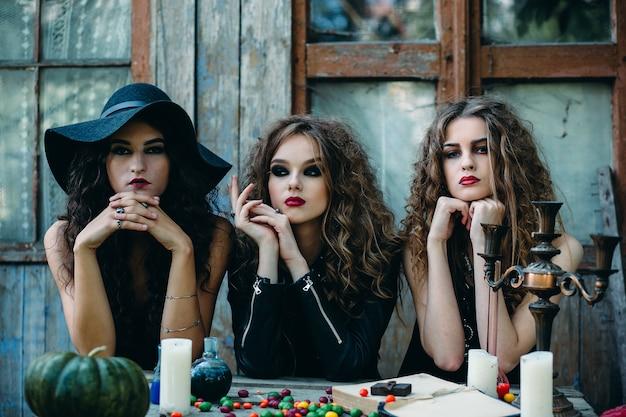 Três bruxas estão sentadas em uma mesa na véspera do halloween