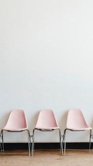 Três cadeiras vazias em rosa pastel em uma sala