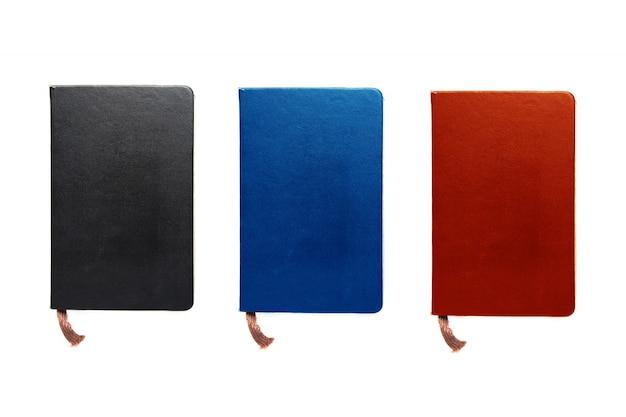 Três cadernos coloridos