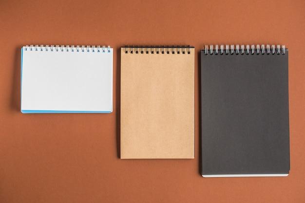 Três cadernos espirais em pano de fundo marrom