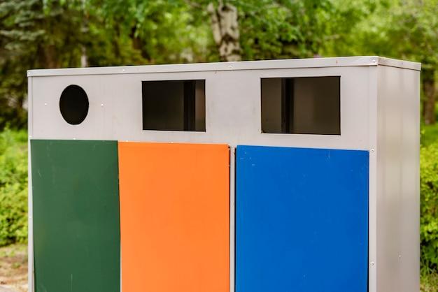 Três caixas de lixo de metal colorido diferentes ou recipientes, classificação de lixo e conceitos de reciclagem