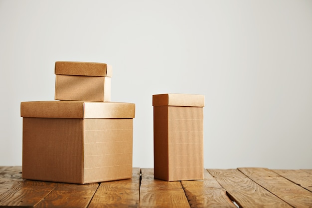 Três caixas de papelão bege de tamanhos diferentes dispostas em cima de uma mesa rústica marrom em um estúdio com paredes brancas