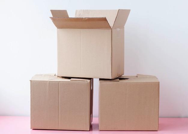 Três caixas de papelão empilhadas em um fundo branco