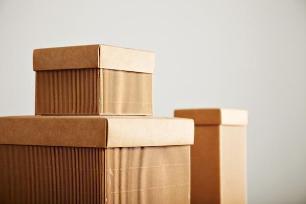Três caixas de papelão ondulado bege semelhantes com tampas de diferentes formas e tamanhos isoladas em branco