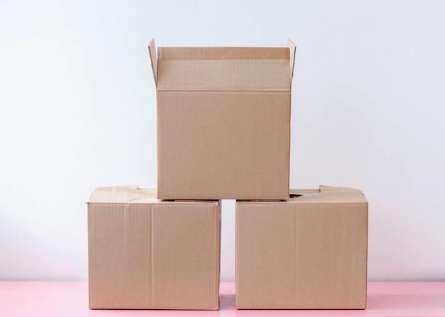 Três caixas de papelão para embalagem estão sobre um fundo branco uma em cima da outra.