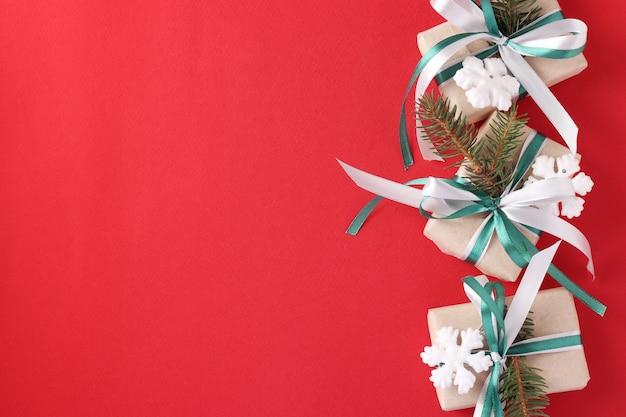 Três caixas de presente de natal com fita verde e branca na superfície vermelha.