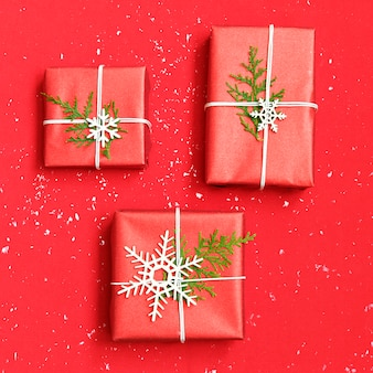 Três caixas de presente de natal decorados e flocos de neve brancos