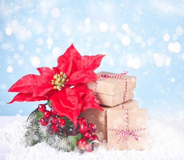 Três caixas de presente de natal e flores de poinsétia. conceito de férias de natal e ano novo.