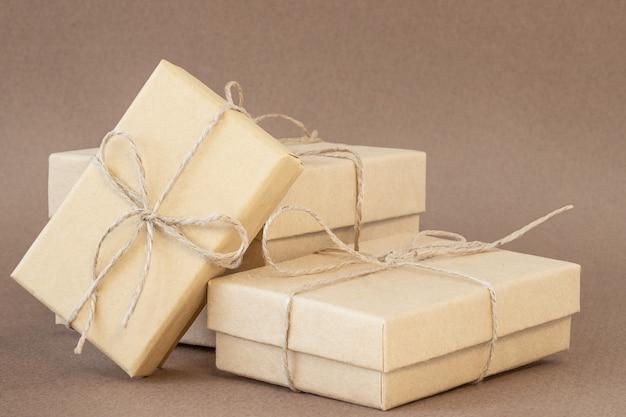 Três caixas de presente ecológicas em fundo marrom