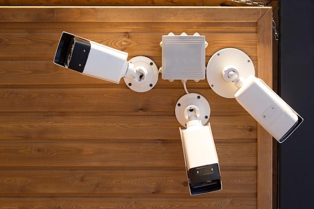 Três câmeras de vigilância sob o teto de madeira.