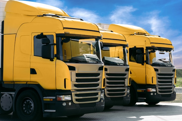 Três caminhões amarelos de uma empresa de transporte