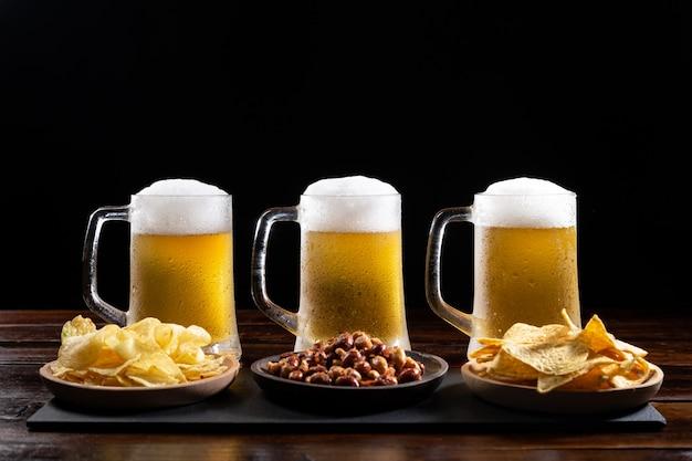 Três canecas de cerveja gelada e pratos com aperitivos na mesa de madeira