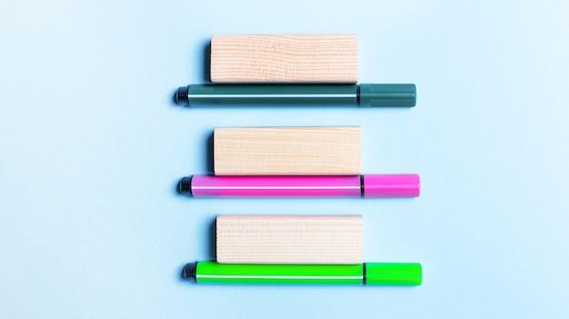 Três canetas hidrográficas multicoloridas e blocos de madeira repousam sobre uma superfície azul clara. modelo