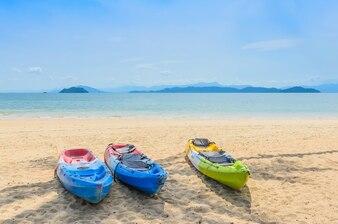 Três canoa colorida na praia de areia com mar azul