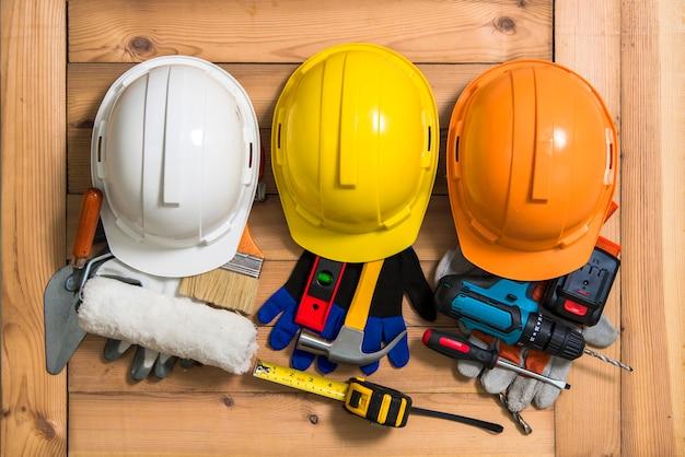 Três capacetes em laranja, amarelo e branco para construção e ferramentas.