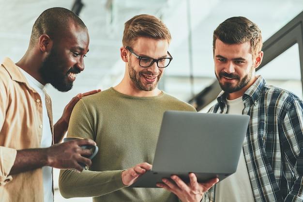 Três caras alegres assistindo algo na tela do laptop