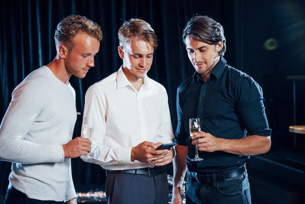 Três caras com roupas festivas conversam e olham para o telefone.