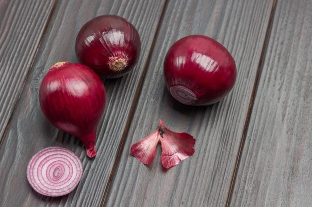 Três cebolas descascadas. fatia de cebola. cebola roxa. fundo de madeira escuro. vista do topo