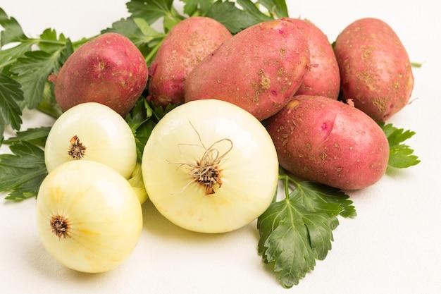 Três cebolas, galho de salsa e tubérculos de batata. fundo branco