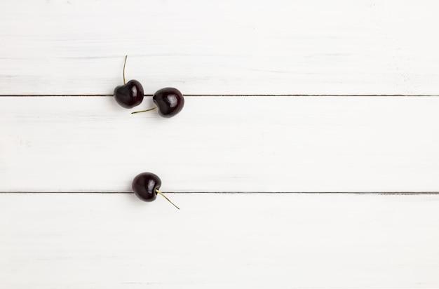 Três cerejas pretas maduras frescas no assoalho de madeira branco da prancha para o fundo.